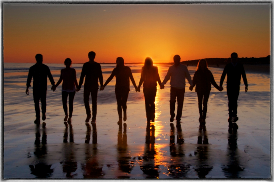 People holding hands at sunset
