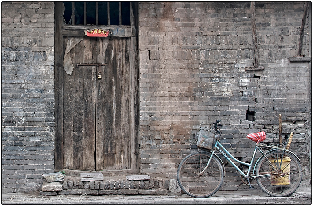 OLD BICYCLE AND DOORWAY, RED-STRIPED SEAT